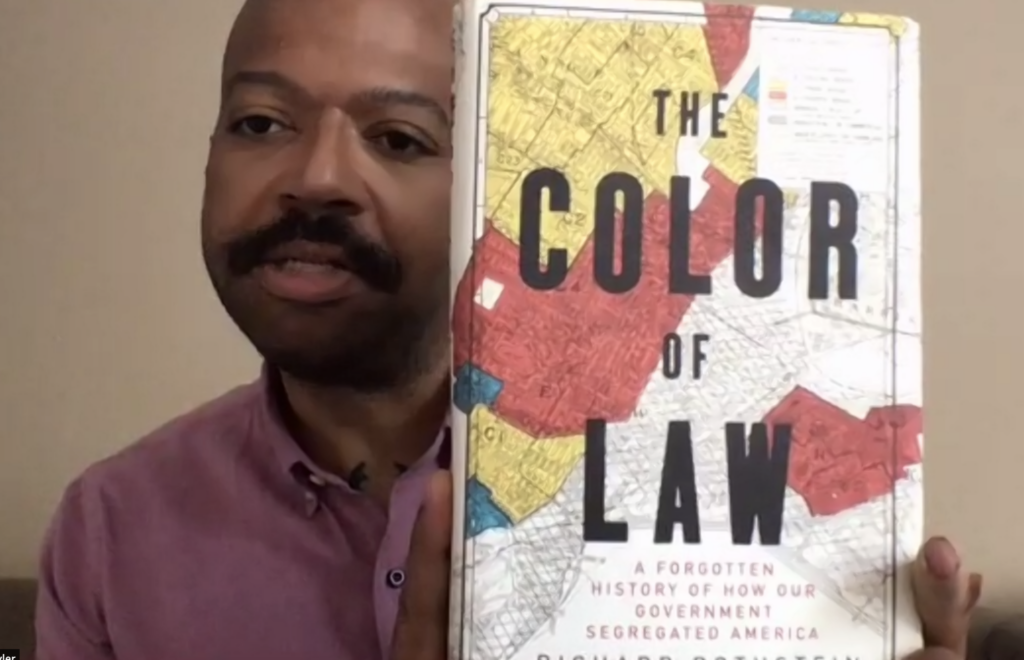 Kevin Tyler showing off the book The Color of Law