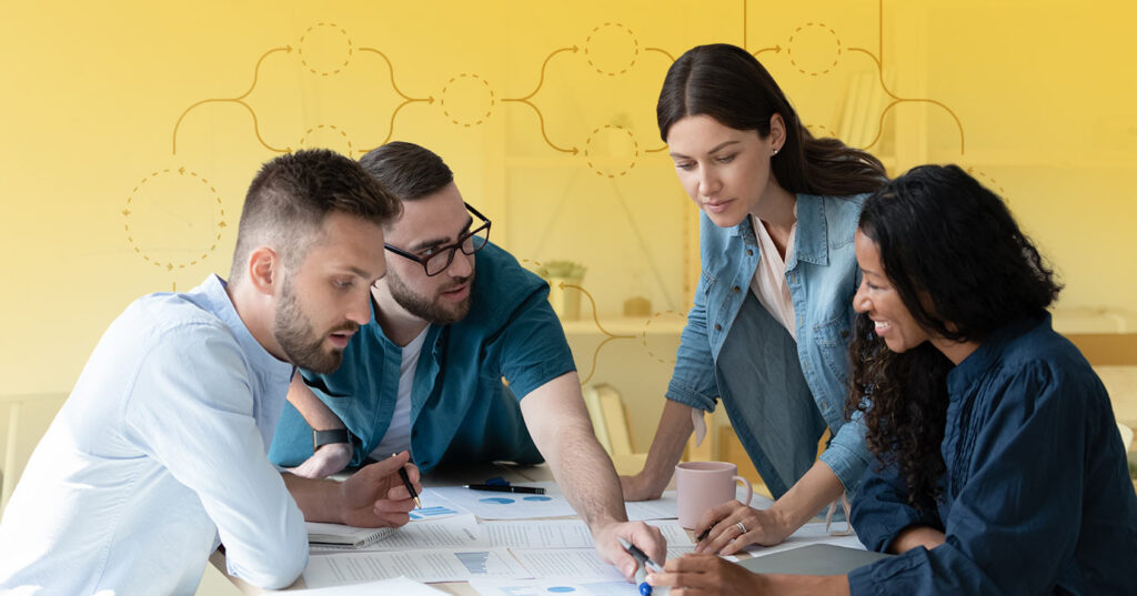 four people looking over business documents on a table to achieve an agile email marketing process